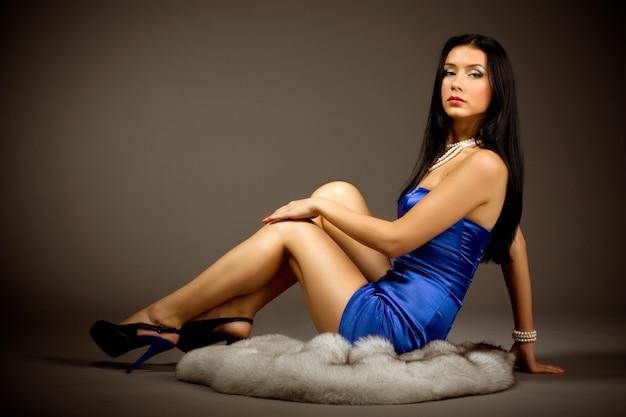Modelo de menina esbelta em um vestido azul de salto