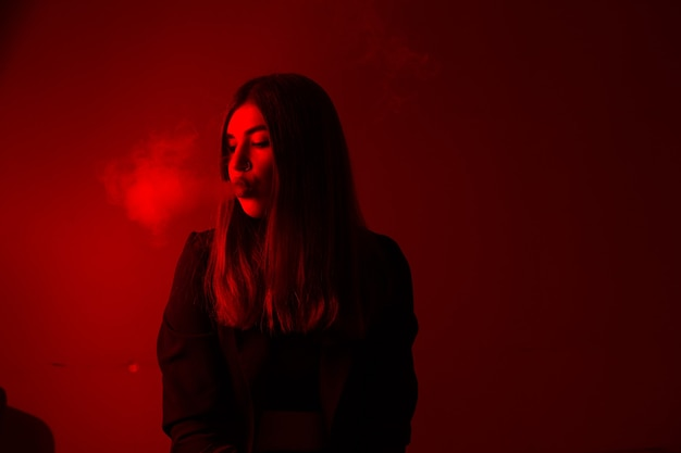 Modelo de menina fuma vapor na luz vermelha.