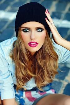 Modelo de menina loira mulher de alta moda look.glamor estilo de vida em jeans casual shorts pano sentado ao ar livre na rua em boné preto em copos