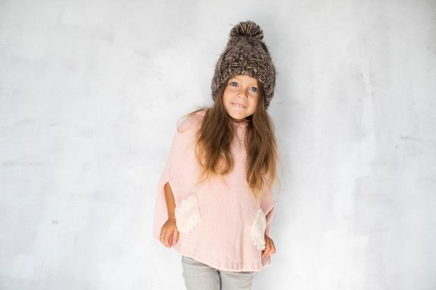 Modelo de menina loira posando na frente de fundo cinza