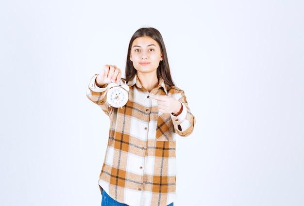 Modelo de menina muito jovem apontando para um despertador.
