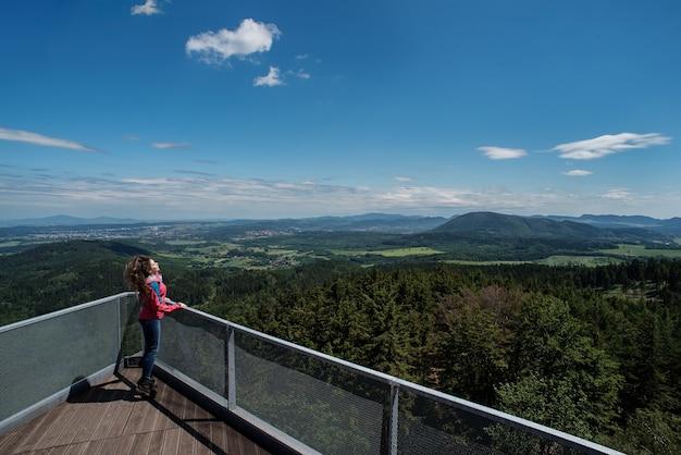 Modelo de menina pulando no deck de observação com vista para as florestas e montanhas.
