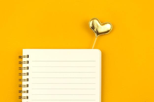 Modelo de mensagem de amor de composição plana leigos com bloco de notas em uma mesa amarela e coração amarelo, foto de vista superior com espaço de cópia