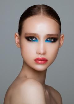 Modelo de moda beleza com maquiagem criativa de olhos pretos e azuis smokey em fundo cinza escuro