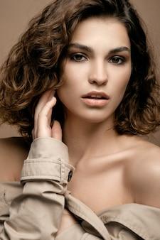 Modelo de moda beleza com pele limpa e cabelos cacheados em manto biege esticar com cachecol