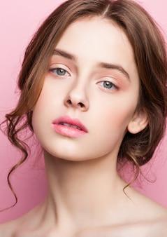 Modelo de moda bonito de beleza com maquiagem natural em fundo rosa