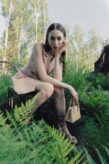 Modelo de moda caucasiano sentado em uma cadeira na floresta cheia de samambaias em uma roupa rosa clássica elegante e uma pequena bolsa bege.