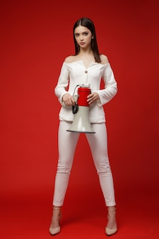 Modelo de moda com megafone em terno branco bela jovem foto de estúdio fundo vermelho