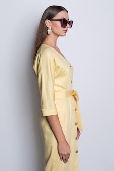 Modelo de moda em grandes óculos de sol com vestido amarelo com botões posando sobre fundo cinza
