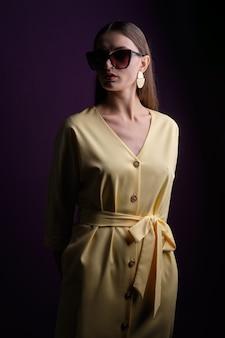 Modelo de moda em grandes óculos de sol com vestido amarelo com botões