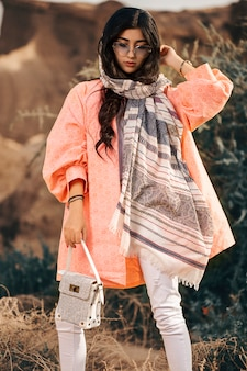 Modelo de moda em jaqueta coral e xale preto com calça branca