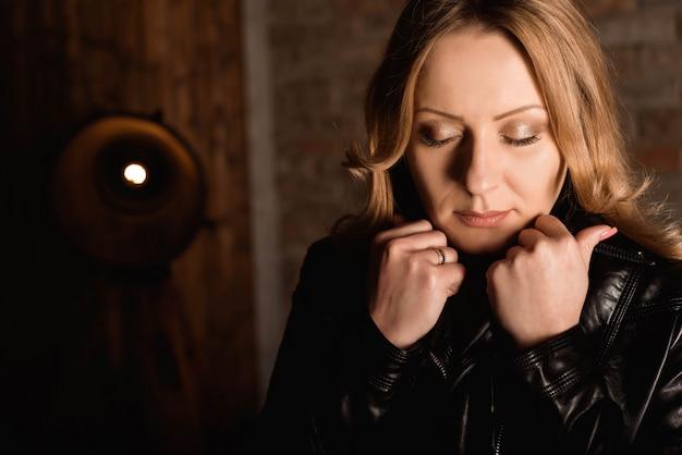 Modelo de moda em uma jaqueta de couro preta posando perto da parede de tijolo