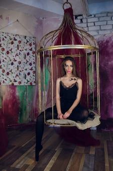 Modelo de moda em vestido de fantasia posando gaiola de aço