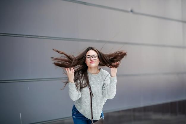Modelo de moda garota em roupas casuais na rua olha para a câmera e toca o cabelo dela