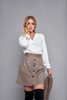 Modelo de moda girl in fashionable clothes on parede cinzenta.