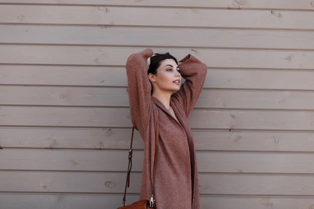 Modelo de moda jovem elegante europeu com casaco de primavera se passando perto de um edifício vintage de pranchas. o modelo de menina elegante adorável na moda alisa o cabelo e desfruta de um descanso perto de uma parede de madeira ao ar livre.