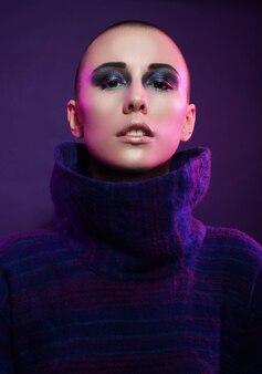 Modelo de moda jovem posando no estúdio. careca. maquiagem brilhante. sobre o fundo rosa.