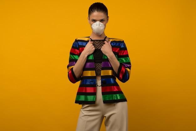 Modelo de moda linda garota magro posando em um respirador protetor em um espaço amarelo. jaqueta colorida do arco-íris da comunidade lgbt
