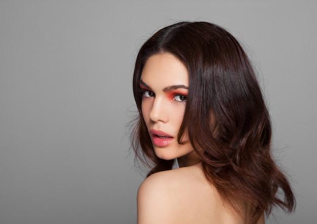 Modelo de moda maquiagem olhos vermelhos e lábios de beleza em fundo cinza