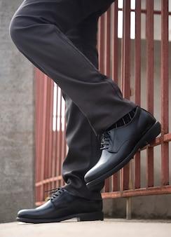 Modelo de moda masculina em pé com sapatos pretos de couro.