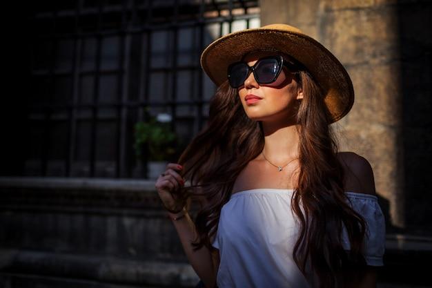 Modelo de moda. retrato ao ar livre do turista jovem bonita usando chapéu de palha e óculos de sol ao pôr do sol.