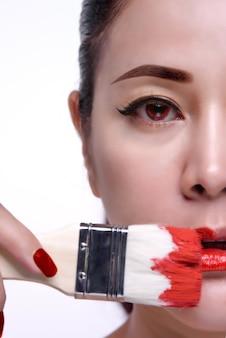 Modelo de mulher asiática com unhas vermelhas, lábios e pincel de cor vermelha