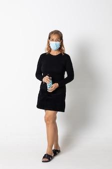 Modelo de mulher asiática de seinor usando máscara protetora em pé isolado no fundo branco.