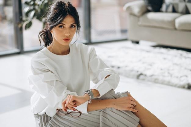 Modelo de mulher atraente jovem sentada no chão na sala de estar