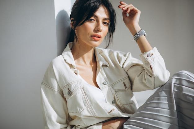 Modelo de mulher atraente jovem sentado junto à parede