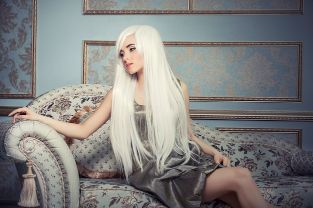 Modelo de mulher bonita com cabelo longo branco platinado na parede do interior
