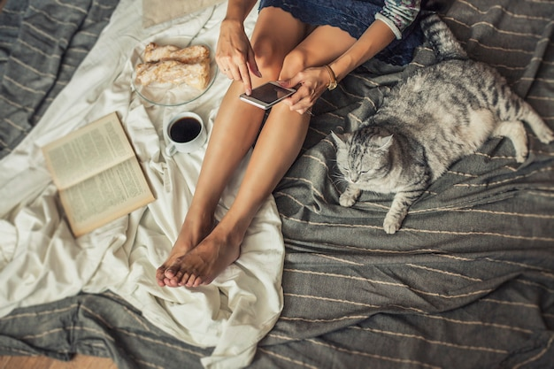 Modelo de mulher bonita com café, bolos, telefone em casa no cobertor com um gato. café da manhã, manhã, casa, conforto