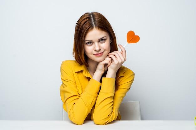 Modelo de mulher bonita com um pirulito de coração à mesa em uma camisa amarela coloca emoções diferentes. dia dos namorados
