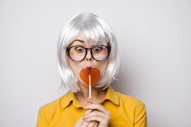 Modelo de mulher bonita com um pirulito de coração à mesa em uma camisa amarela coloca emoções diferentes.