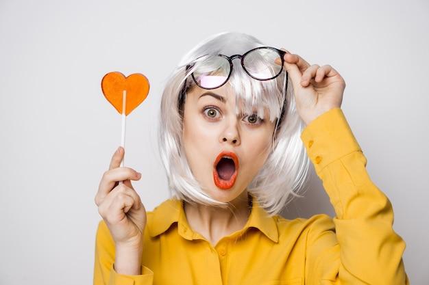Modelo de mulher bonita com um pirulito de coração na mesa em uma camisa amarela apresenta emoções diferentes