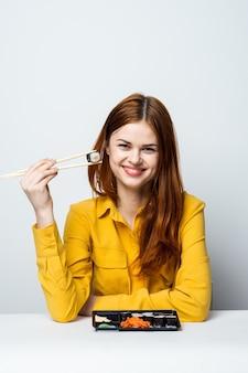 Modelo de mulher bonita comendo sushi e pãezinhos da entrega de comida na mesa em uma camisa amarela posando