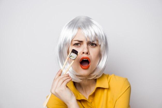 Modelo de mulher bonita comendo sushi e pãezinhos durante a entrega de comida na mesa com uma camisa amarela e apresentando emoções diferentes