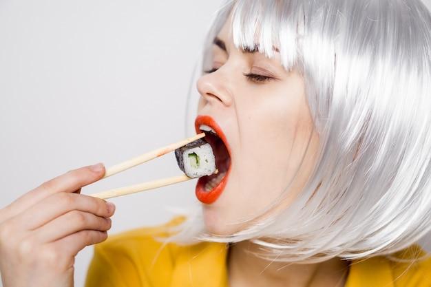 Modelo de mulher bonita comendo sushi e rolos de entrega de comida à mesa em uma camisa amarela, posando de emoções diferentes