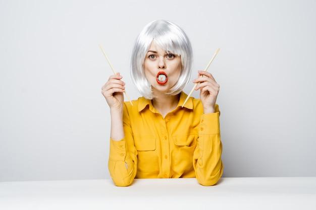 Modelo de mulher bonita comendo sushi e rolos de entrega de comida à mesa em uma camisa amarela