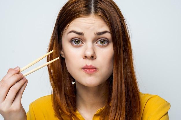 Modelo de mulher bonita comendo sushi e rolos de entrega de comida na mesa em uma camisa amarela