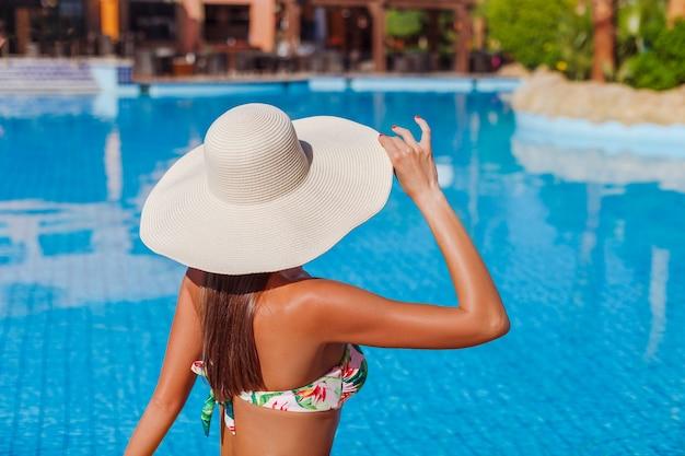 Modelo de mulher bonita e sexy de biquíni relaxando na piscina
