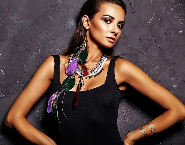 Modelo de mulher bonita em lingerie preta de verão com maquiagem criativa brilhante posando perto de parede cinza
