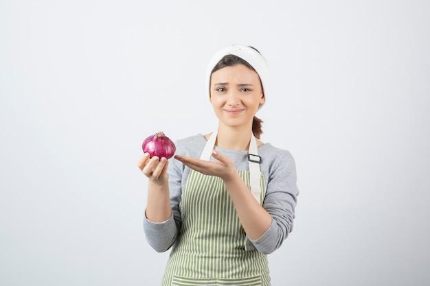 Modelo de mulher bonita no avental segurando uma cebola roxa.