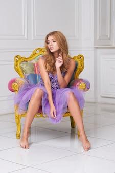 Modelo de mulher bonita posando em um vestido elegante no estúdio.