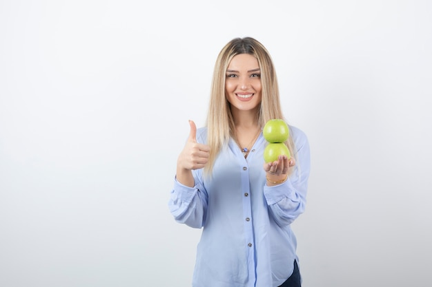 Modelo de mulher bonita segurando maçãs frescas e aparecendo um polegar.
