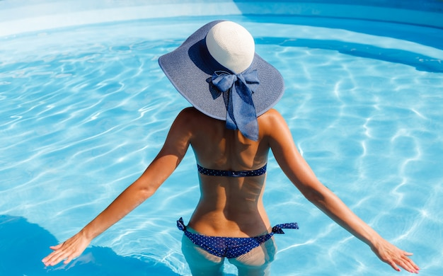 Modelo de mulher bonita sexy em biquíni é relaxante na piscina