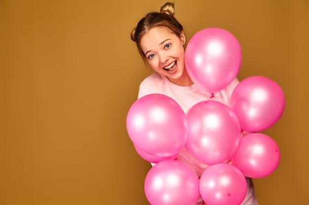 Modelo de mulher com balões de ar rosa na parede dourada