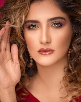 Modelo de mulher com cabelos loiros encaracolados e maquiagem chique