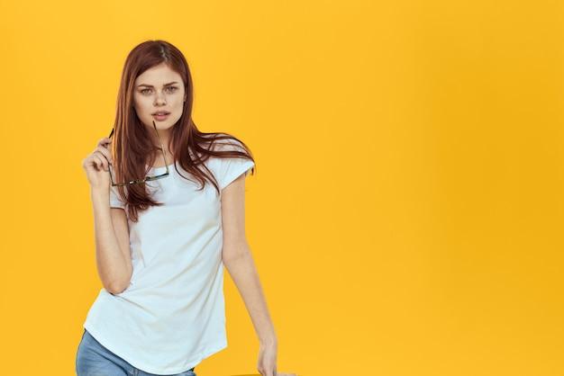Modelo de mulher de jeans e uma camiseta branca posando em uma parede colorida