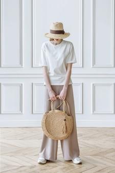 Modelo de mulher elegante com chapéu segura a bolsa nas mãos em cena branca no estúdio