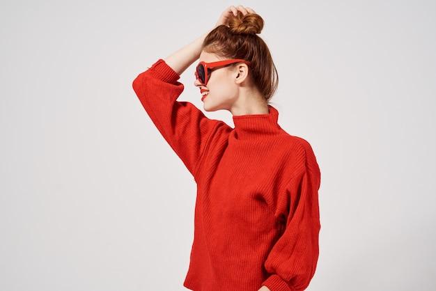 Modelo de mulher elegante com suéter vermelho e óculos de sol gesticulando